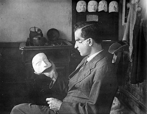 A wounded soldier examining the beginnings of his facial mask (image: The Imperial War Museum).