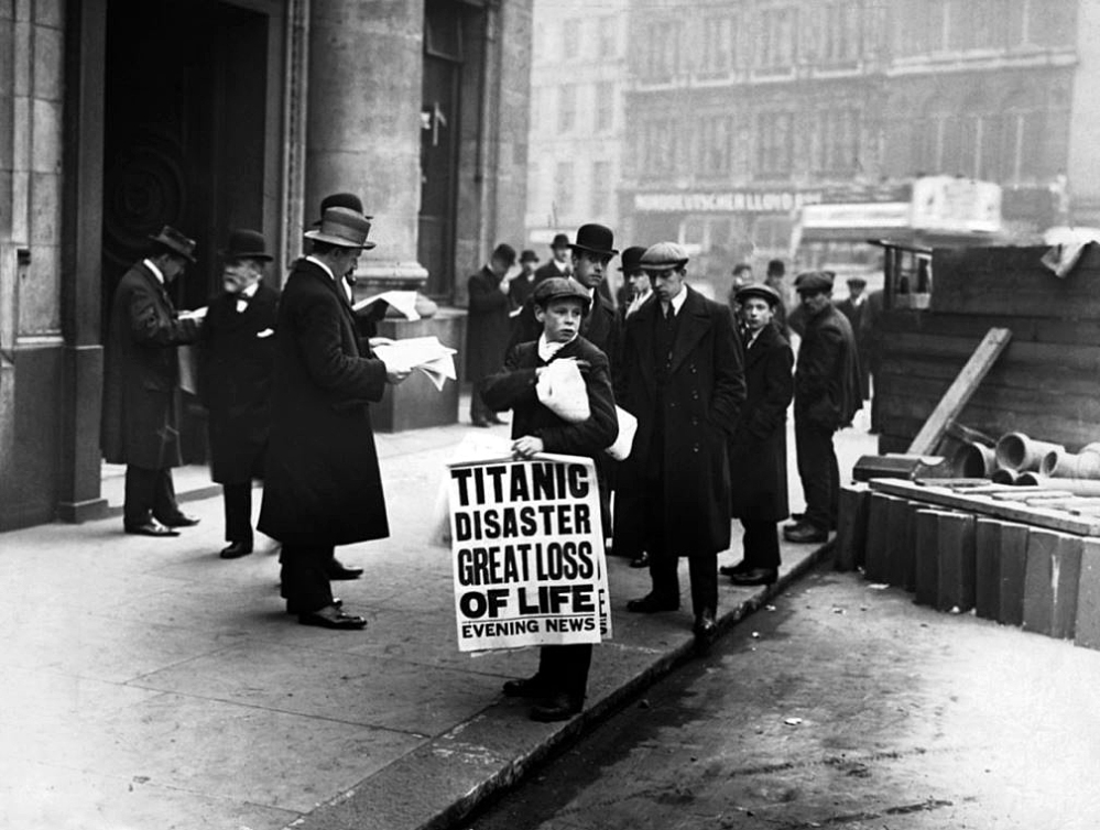 Newspaper boy bearing the  awful headline outside White Star's London office